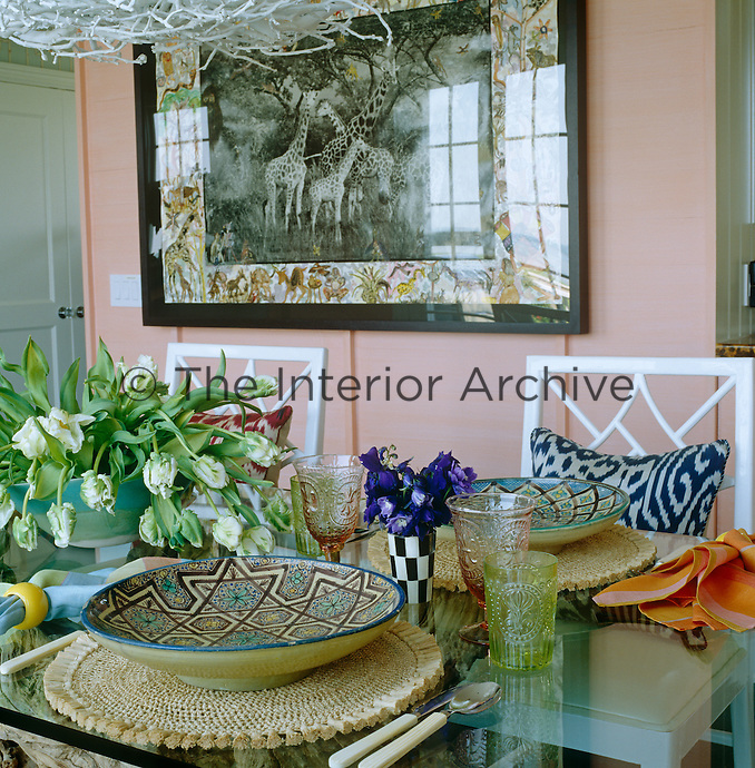 Detail of a laid table with hand-painted patterned plates and a hand-coloured photograph by Peter Beard hanging on the wall