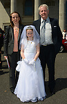 Michaela McShane with her Mum Paula and Granddad Eugene after she made her First Communion at the Lourdes Church on Saturday. www.newsfile.ie