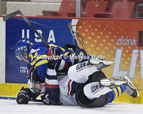 Robin Figren 16 of Sweden falls on Mark Mitera 7 of the United States.  Team USA White defeated Team Sweden 5-3 on Friday, August 11, 2006, at the 1980 Rink in Lake Placid, New York in their final game of the US Under-20 Training Camp and Summer Hockey Challenge.