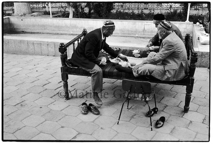 Uzbekistan - Ferghana Valley - Old men drinking tea on the sori, the traditional uzbek table and rest area.