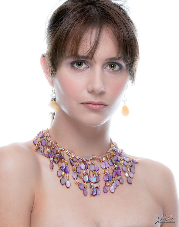 Beautiful brunette model, wearing a purple necklace and gold earrings closeup