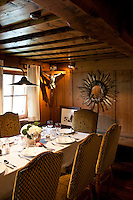 The wood panelled dining room has a low beamed ceiling with a table laid for dinner