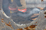 Firefighter at a fire scene blurred inside a melted greenhouse building with smoking embers around the firemans boots
