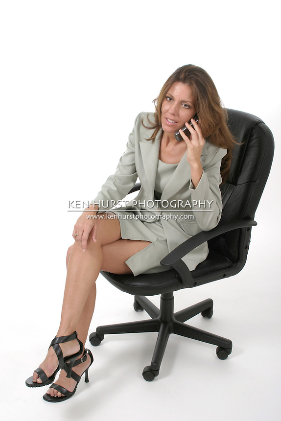 Attractive and beautiful executive business woman with very distracting legs sitting in office chair talking on cellphone.