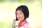 Young Asian girl with flowers with shallow depth of field