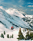 USA, Utah, friends sitting on Little Cloud Ski Lift with views to Salt Lake City, Snowbird Ski Resort