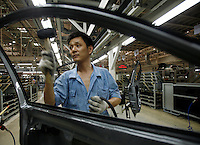 Workers assemble automobiles at the Shanghai Volkswagen (SVW) plant in Shanghai, China.