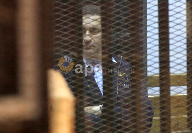 "Alaa Mubarak, the son of former former president Hosni Mubarak stands in a courtroom cage during his retrial in Cairo on April 16, 2015. Cairo Criminal Court held at Police Academy will resume, Gamal and Alaa Mubarak trial in ""Stock Market Manipulation"" case. Gamal and Alaa Mubarak and six other businessmen, who are officials and former members of the board of directors of the National Bank face charges of illegal gains from the sale of National Bank of Egypt, waste of public money, causing huge losses to the economy and destroying the country's banking system through manipulating the stock exchange. Photo by Stringer"