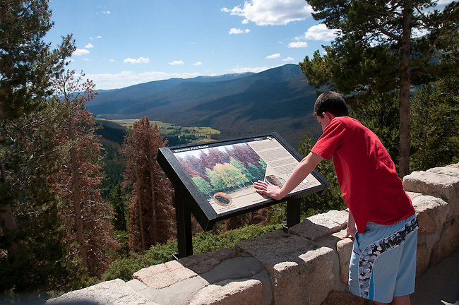 visitor, teen, boy, interpretive sign, Farview Curve, NPS, information, August, summer, afternoon, Trail Ridge Road, above Kawuneeche Valley, Rocky Mountain National Park, Colorado, USA