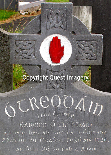 A Celtic headstone that includes the UDA,  Ulster Defence Association (a bloody red hand) at Milltown Cemetery, an established landmark of Nationalist Belfast, is often identified outside the realms of normal everyday burials, with the conflict of the past thirty years. Being the main Catholic burying ground for the city it is intertwined into the legacy of conflict. <br />