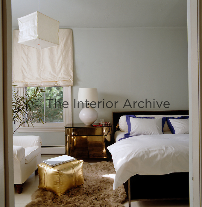 A 1940s French mirrored bedside table, gold ottoman and sheepskin rug add a touch of glamour to the bedroom