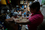 Deaconess Irene Lagahit Vioya leads a group of children in praying for a sick man in his home in a neighborhood in Manila, Philippines. A graduate of Harris Memorial College, she works on the staff of Knox United Methodist Church.