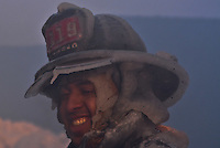 A firefighter from Tower Ladder 119 is cased in ice after operating at a seven alarm warehouse fire.