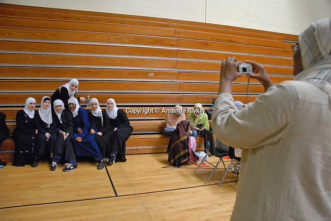 "Students from the Al-Huda High School in Patterson, New Jersey pose for their coach as the Islamic Games women's events kicked off in South Brunswick, New Jersey on May 26, 2007.  The event website promised that ""If you can pray in it, you can play in it""; over 600 youths from five states participated in the event."