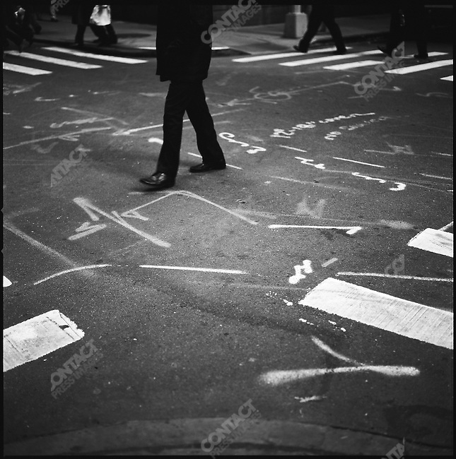 Pedestrians crossed a maze of painted instructions on a crossroads on Exchange Place in Downtown Manhattan. New York City, New York, November 24, 2008