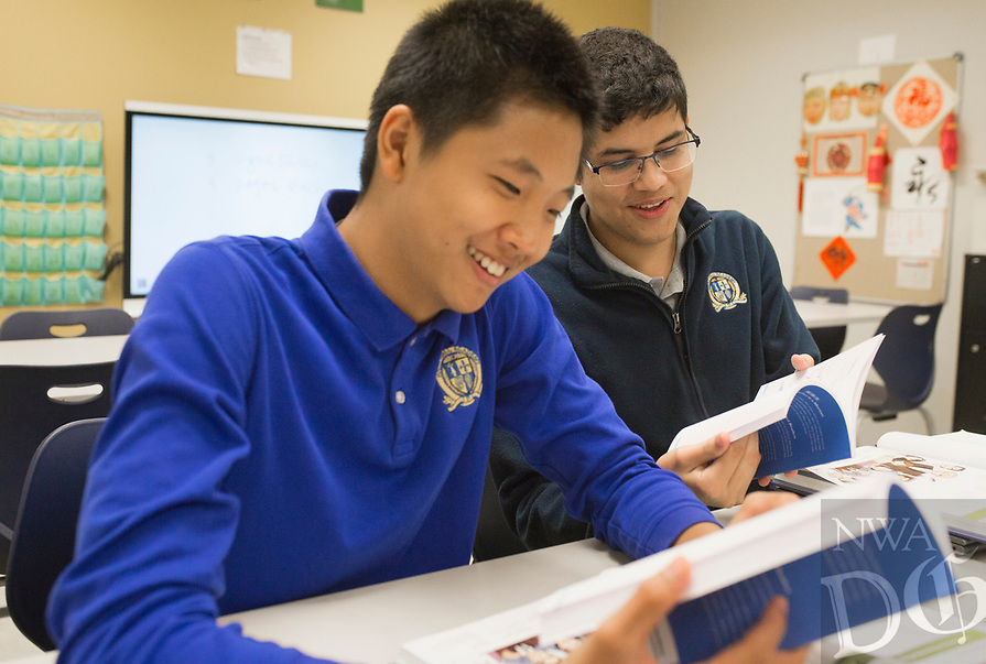 """NWA Democrat-Gazette/CHARLIE KAIJO Victor Gao, 15, of Bentonville and Mauricio Carvajal Villasenor, 17, of Bentonville (from left) look at their Mandarin text books, Friday, August 9, 2019 at Haas Hall Academy in Bentonville.<br /> <br /> """"There's more pathways for you,"""" said Victor Gao, explaining why he chose Mandarin to study. """"You can choose more careers especially if you want to be a doctor or get in to business."""" Haas Hall held their second day of classes."""