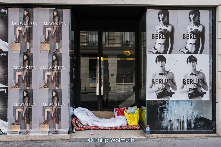 Bedding and possessions of a homeless rough sleeper in the doorway of an empty shop, Paris, France