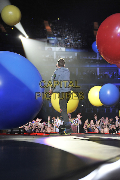 Chris Martin.Coldplay performing live in concert, O2 Arena, Greenwich, London, England. .9th December 2011.stage gig performance music full length blue jacket  black singing back behind rear fans crowd audience balloons .CAP/MAR.© Martin Harris/Capital Pictures.