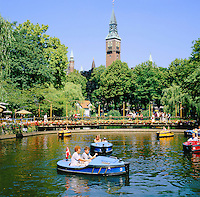 Denmark, Zealand, Copenhagen: Tivoli Gardens, boats on lake below tower of the Radhus (Town Hall) | Daenemark, Insel Seeland, Kopenhagen: Der Tivoli, ein weltbekannter Vergnuegungs- und Erholungspark, im Hintergrund das Rathaus