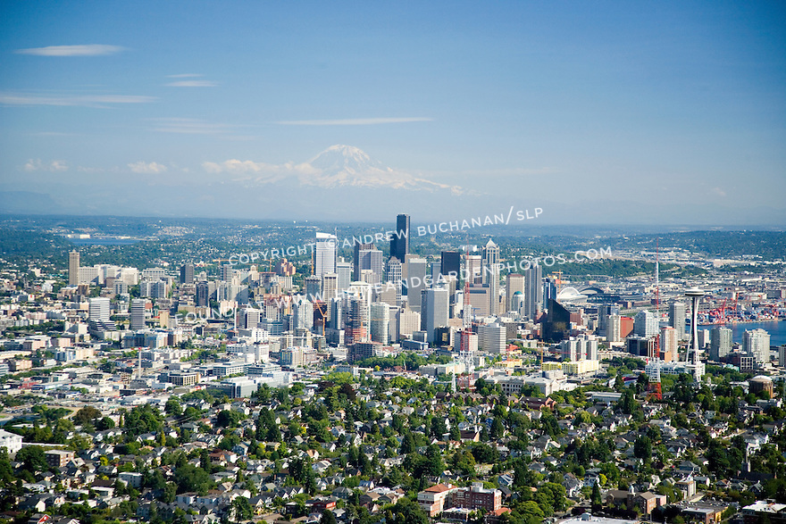 A sunny, summer afternoon aerial photo of Seattle, Washington showing green and leafy Queen Anne Hill in the foreground, the skyscrapers of the downtown skyline, and snow-capped Mount Rainier in the distance in this classic image of a modern Northwest city.