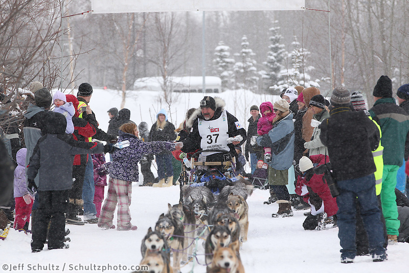 Scott Janssen Mushes through Bike/ski trail in midtown Anchorage, During the 2012 Iditarod ceremonial start..Britt Coon/Iditarodphotos.com.