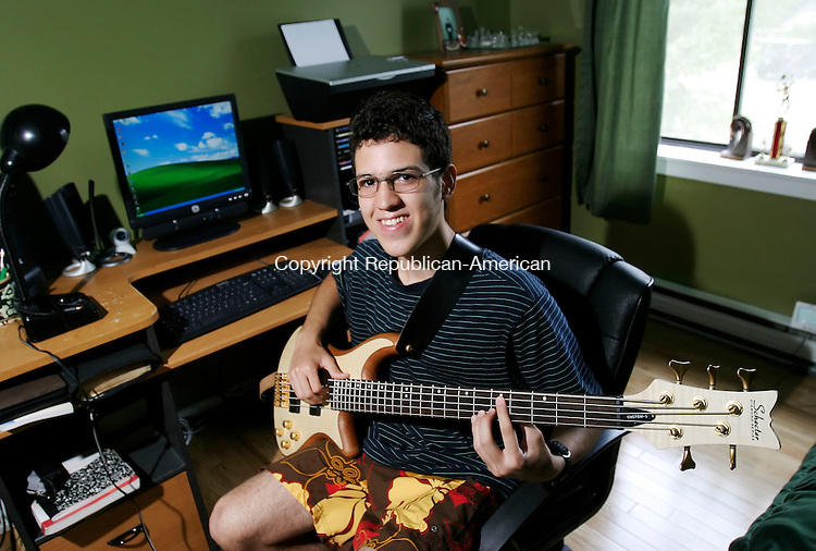 NAUGATUCK, CT, 22 June 2006- 062206BZ02- Stanley Fofano, 17, gr. 11 at Naugatuck High School, poses in the bedroom of his Naugatuck home with his Schecter Diamond Series 5-string bass.  Fofano, who only spoke Portuguese when he came to the United States three years ago, said he plays the bass in church.<br /> Jamison C. Bazinet Republican-American