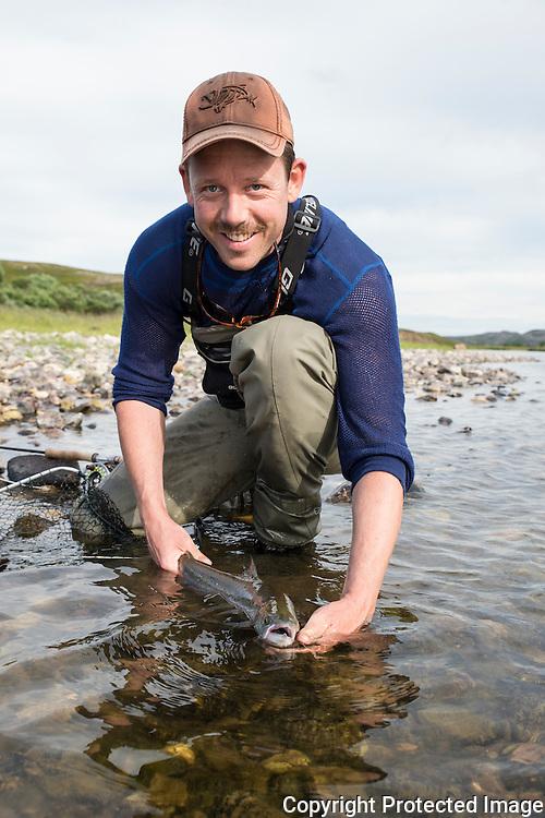 Mann setter ut smålaks i Komagelva. ---- Man releasing small salmon in Komagelva.