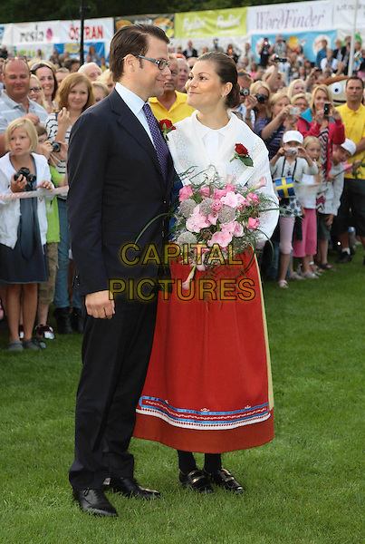 DANIEL WESTLING & CROWN PRINCESS VICTORIA OF SWEDEN .At the celebration of Crown Princess Victoria of Sweden's 32nd Birthday, .Borgholm Stadium, Öland, Sweden, .14th July 2008..royal royal family royals full length red  flowers traditional costume skirt dress couple black suit tie glasses .CAP/PPG/WS.©Willi Schneider/People Picture/Capital Pictures