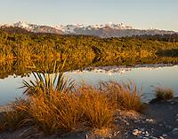 Sunset views of Southern Alps with Aoraki Mount Cook, Mount Tasman and Franz Josef Glacier over coastal lagoon with reflections, Westland Tai Poutini National Park, UNESCO World Heritage Area, West Coast, New Zealand, NZ