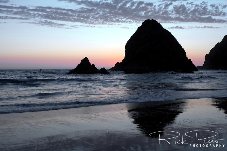 Whaleshead Rock reflects in the sands of Whaleshead Beach in Southern Oregon north of the town of Brookings. Whales Head Rock is a sea stack that resembles the head of a whale. When a wave hits a channel cut into the sea stack it spurts spray that looks like a whale spouting.
