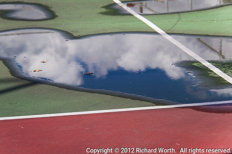 The straight geometry of lines on a tennis court are interrupted by the random shapes of puddles reflecting the equally random shapes of clouds.