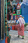 A traditional dressed Moroccan woman walks in the old town (medina) of Chefchaouen in Morocco.