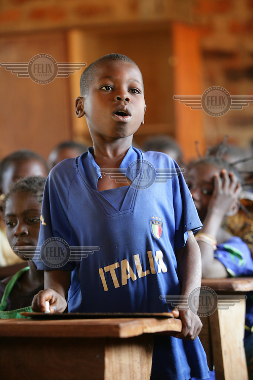Boy wearing an Italia football jersey in class at a community school.