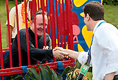 Washington, DC - June 25, 2009 -- White House Press Secretary Robert Gibbs (L) shakes hands with Associated Press reporter Ben Feller after Feller knocked Gibbs into a dunk tank before a luau for members of Congress and their families on the South Lawn of the White House June 25, 2009 in Washington, DC. In a celebration of U.S. President Barak Obama's home state, the South Lawn was decorated with tiki torches and palm huts and the meal prepared by famous Hawaiian chef Alan Wong.  .Credit: Chip Somodevilla - Pool via CNP