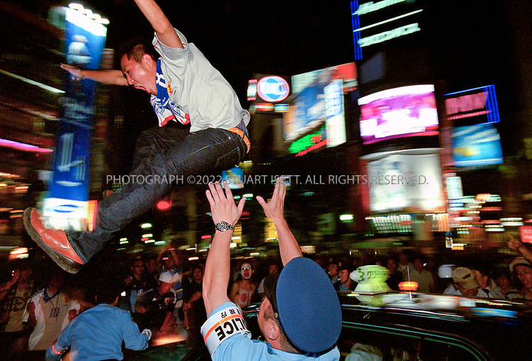 6/9/2002--Tokyo, Japan.A Japan team fan jumps from the roof of a taxi as a policeman attempts to stop him. The fan was later arrested. Jubilant fans of the Japanese national team came by the thousands across Japan to chant and clap hands as they celebrate Japan's first victory in the World Cup Sunday night in Tokyo's Shibuya  district. Japan beat Russia 1-0 in the 1st round Group H match...All photographs ©2003 Stuart Isett.All rights reserved.This image may not be reproduced without expressed written permission from Stuart Isett.