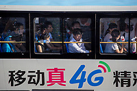 People ride a bus with an advertisement for 4G cellular phone service in Xian, Shaanxi, China.