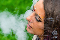 Young woman smoking marijuana in a pipe, LIttleton, Colorado USA.