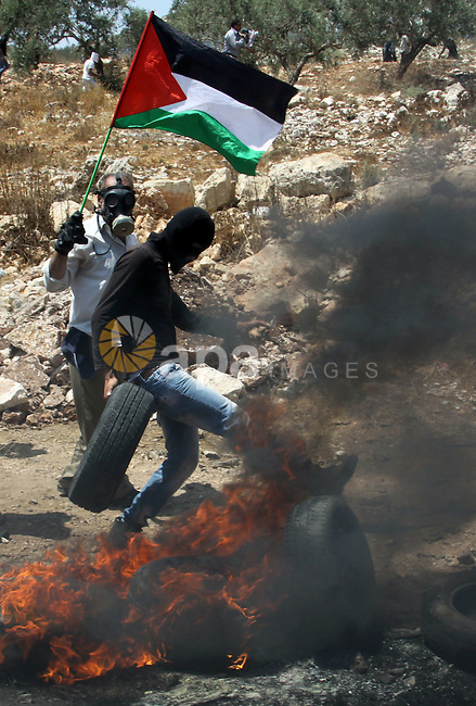 A Palestinian protestor sets a tyre on fire during clashes with Israeli troops following a weekly protest against the Jewish settlement of Kdumim, near Nablus,in the northern West Bank village of Kufr Qaddum, June 29, 2012. Photo by Nedal Eshtayah