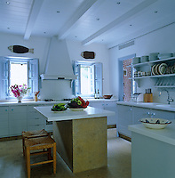 The clean contemporary kitchen has small windows with pale blue shutters and white work surfaces