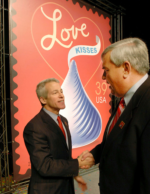 "Chairman, President and Chief Executive Officer The Hershey Company Richard Lenny, left, shakes hands with the Postmaster General John Potter, right, following the unveiling of the new U.S. Postal Service ""With Love and Kisses"" stamp celebrating the 100th Anniversary of Hershey's Kisses chocolates Saturday, Jan. 13, 2006 in Hershey, Pa. The ""With Love and Kisses"" stamp features a Hershey's Kisses Chocolate and a red heart that form mirror images of one another. (AP/The Hershey Company/Bradley C Bower)"