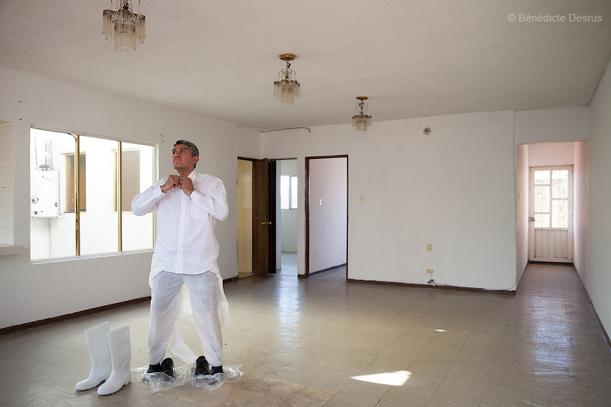 """Donovan puts on his Hazmat suit before beginning the cleanup of an unsolved homicide in Cuernavaca, Morelos – one of Mexico's most dangerous cities on August 7, 2015. The 66-year-old victim was a retired economics lecturer from the local university, and was killed in January of this year. The cleanup took place eight months later. The victim's family has since moved away to avoid further trouble. They remarked that justice is slow in Mexico and expressed dissatisfaction with the police investigation, but appreciated Donovan's discretion and professionalism. Donovan Tavera, 43, is the director of """"Limpieza Forense México"""", the country's first and so far the only government-accredited forensic cleaning company. Since 2000, Tavera, a self-taught forensic technician, and his family have offered services to clean up homicides, unattended death, suicides, the homes of compulsive hoarders and houses destroyed by fire or flooding. Despite rising violence that has left 70,000 people dead and 23,000 disappeared since 2006, Mexico has only one certified forensic cleaner. As a consequence, the biological hazards associated with crime scenes are going unchecked all around the country. Photo by Bénédicte Desrus"""