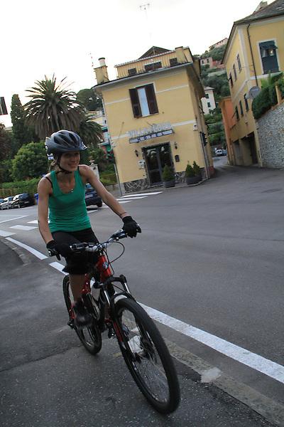Woman biking in front of our hotel in Bogliasco, Genova, Italy.