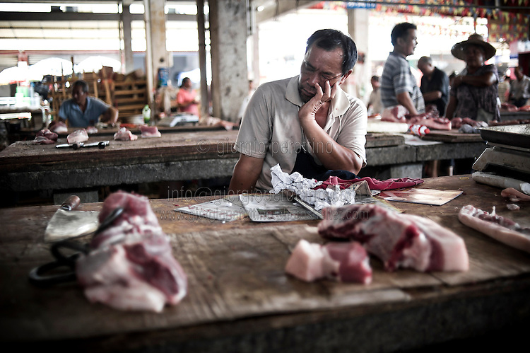 """A Chinese butcher takes a rest in a village market near YangShuo, Guilin, China, August 02, 2014. <br /> <br /> This image is part of the series """"24/7"""", an ironic view on restless and fast-growing Chinese economy described through street vendors and workers sleeping during their commercial daily activity. <br /> <br /> © Giorgio Perottino"""