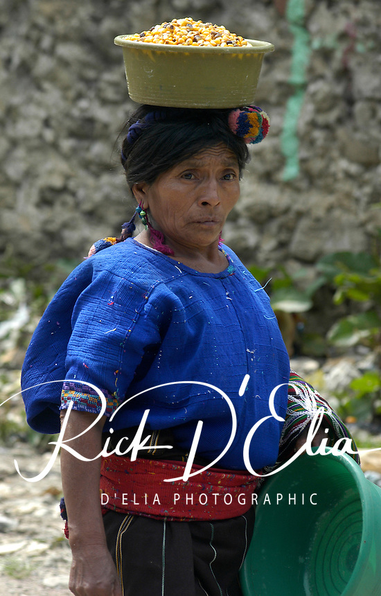 A Ixil Mayan woman carries fresh-picked coffee beans in from the farm in Chajul, Guatemala. The highlands of Guatemala are a favorite source of coffee bean in the world. It is often picked from the highland farms one basket at a time. Most indigenous women of the Western Guatemala Highlands wear the traditional clothing of their villages rather than adopting western styles the are prevalent in the large cities.