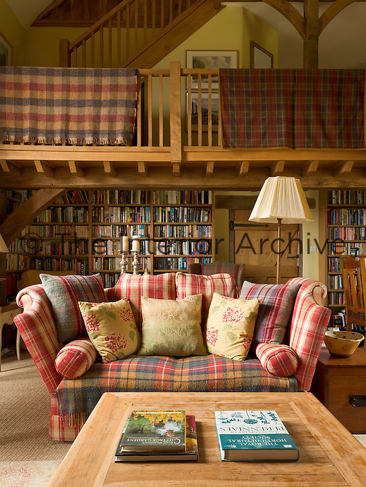In the double-height living area bookshelves have been  built under the gallery forming an extensive library and a staircase extends to the attic above