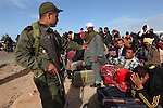 An Egyptian man covers his face while a soldier tries to calm another person at the Tunisia-Libya border near Ben Guerdane, Tunisia, Friday, Feb. 26, 2011. Thousands of foreign workers continued their exodus across the border into Tunisia, fleeing violence sparked by an uprising against Col Muammar Qaddafi. The refugees, primarily Egyptians, had to wait at the border or at an improvised camp nearby until a bus could take them to the airport in Tunis, but the number of people waiting far exceeded the seats available on the buses.