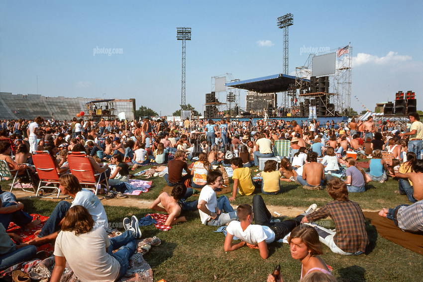 """Wide view of the ball field facing the stage. Deadheads and fans relaxing before the Grateful Dead Concert begins later in the day as the sun grows warmer. At Roosevelt Stadium on 4 August 1976. Showing entire sound array of Hard Truckers Speakers. This image appears in DK Publishers """"The Illustrated Trip"""" The Grateful Dead as a 2 page spread."""