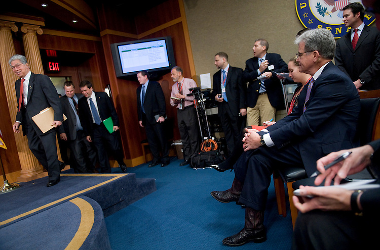 Sen. Tom Coburn, R-Okla., right, watches the arrival of Sens. Daniel Akaka, D-Hawaii, Jon Tester, D-Mont., and Mark Begich, D-Alaska, to a news conference to call on the Senate to pass the Caregivers and Veterans Omnibus Health Services Act of 2009, Nov. 9, 2009.  The legislation being blocked Sen. Coburn.