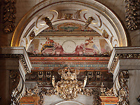 Detail of the allegorical trompe l'oeil ceiling fresco painted by Antonio Simoes Ribeiro and Vicente Nunez in the Red Room, and gilded crown and arch separating Red and Black Rooms, in the Joanina Library, or Biblioteca Joanina, a Baroque library built 1717-28 by Gaspar Ferreira, part of the University of Coimbra General Library, in Coimbra, Portugal. The Casa da Livraria was built during the reign of King John V or Joao V, and consists of the Green Room, Red Room and Black Room, with 250,000 books dating from the 16th - 18th centuries. The library is part of the Faculty of Law and the University is housed in the buildings of the Royal Palace of Coimbra. The building is classified as a national monument and UNESCO World Heritage Site. Picture by Manuel Cohen