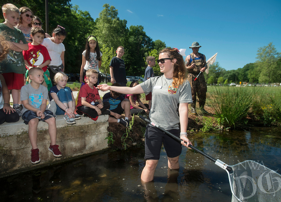 NWA Democrat-Gazette/BEN GOFF @NWABENGOFF<br /> Laura Ellis, who is working on a Ph.D. in biology and is vice president of the Biology Graduate Student Association at the University of Arkansas, shows aquatic life to third grade students from Tillery Elementary in Rogers Thursday, May 17, 2018, at Lake Atalanta in Rogers. All the third grade classes from Tillery took part in the field trip, with the graduate students helping children explore nature and ecosystyms with a variety of hands-on activities as part of their community outreach efforts.